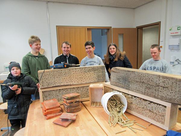 Schüler mit Bienenhotel aus Bambusröhrchen und Ziegeln